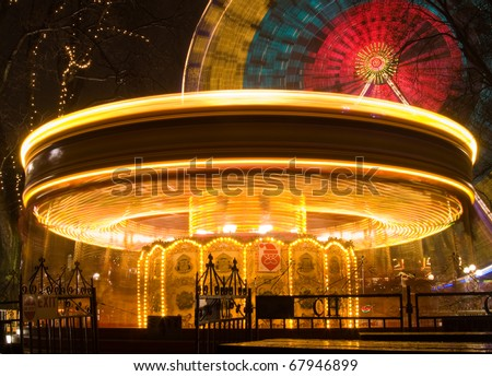 Merry go round lit up at night with Ferris wheel in background - stock photo
