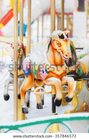 Merry-go-round retro carousel horses covered with snow in winter city park entertainment, vertical. An abandoned amusement. - stock photo