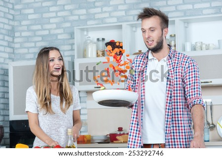 Merry joint cooking. Young and beautiful couple in love preparing meals in the kitchen and look at each other while standing in the kitchen and throw the food in the pan - stock photo