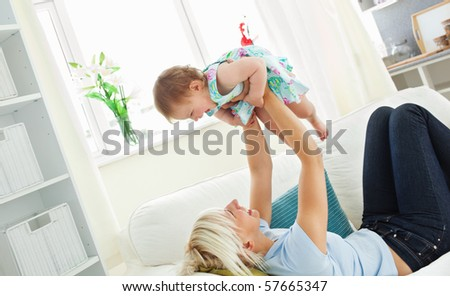 Merry mother playing with her daughter in living room - stock photo