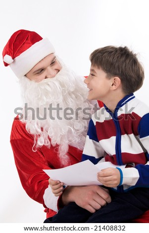 Merry Santa holding little boy on hands while he reading his letter - stock photo