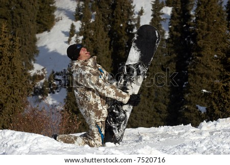 Merry snowboarder play the fool on ski slope - stock photo