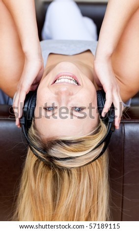 Merry woman lies on a brown sofa and listen music with headphones - stock photo