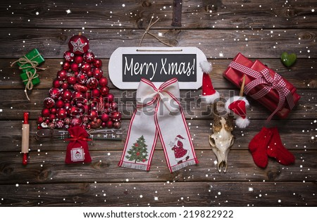 Merry xmas text on wooden sign with classic red christmas decoration on wood. - stock photo