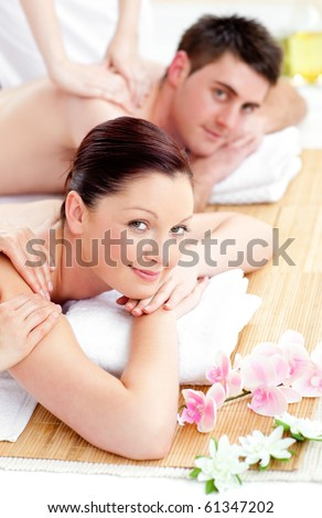 Merry young couple enjoying a back massage in a spa center - stock photo