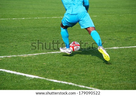 MERSIN, TURKEY - FEBRUARY 23: Turkey League soccer match in Mersin February 23, 2014. A football player close up kicking the ball with the green pitch on the background.