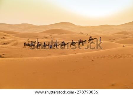 MERZOUGA, MOROCCO, APRIL 13, 2015: Tourists visit Dunes Erg Chebbi near Merzouga during a camel excursion - stock photo