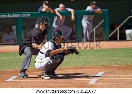 MESA, AZ - OCTOBER 18: Pittsburgh Pirates catching prospect Tony Sanchez and umpire Darren Budahn participate in an Arizona Fall League game Oct. 18, 2010 at Mesa's HoHoKam Stadium, Arizona. - stock photo
