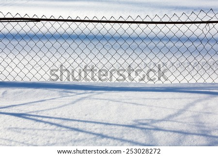mesh fence in deep snow in the winter - stock photo