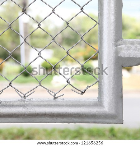 Mesh fence with silver border - stock photo