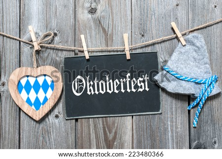 Message, bavarian hat and heart hanging on the clothesline against wooden board. Background for Oktoberfest - stock photo