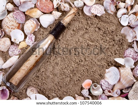 Message in a bottle on a sandy beach surrounded by seashells - stock photo