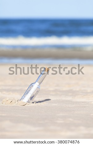 Message in a bottle on beach, shallow depth of field. - stock photo