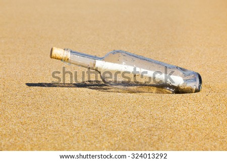 Message in a clear glass corked bottle partially buried in beach sand conceptual of a love letter from a sweetheart or plea for help form a shipwreck or marooned sailor carried ashore by the tides. - stock photo