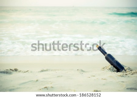 Message in a glass bottle in a solitary beach near the sea  - stock photo