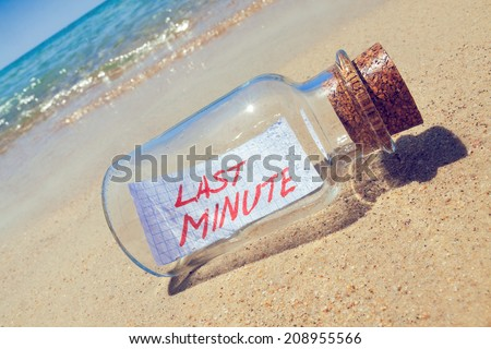 "Message in a vintage bottle ""Last minute"" on beach. Creative summer break and tourism concept."