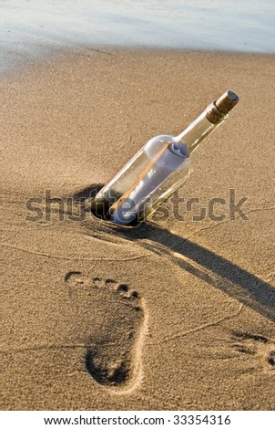 message in bottle with footprint - stock photo