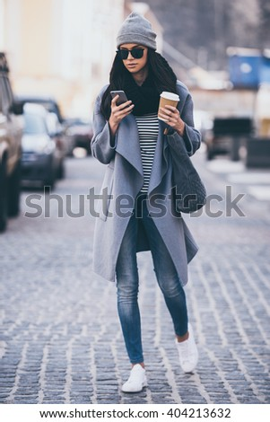 Message on a go. Full length of beautiful young woman in sunglasses using her smart phone while crossing the street - stock photo