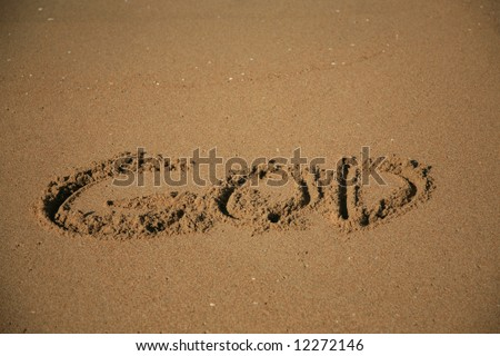 """Message says """"god""""  in the Sand on a Beach with waves and blue ocean concepts - stock photo"""