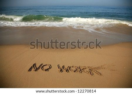 """Message says """"no work""""  in the Sand on a Beach with waves and blue ocean concepts - stock photo"""