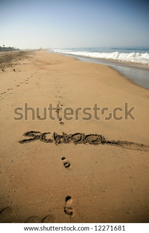 """Message says """"school""""   in the Sand on a Beach with waves and blue ocean concepts - stock photo"""