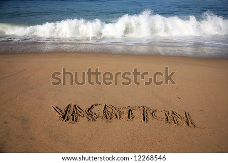 """Message says """"vacation""""  in the Sand on a Beach with waves and blue ocean concepts - stock photo"""