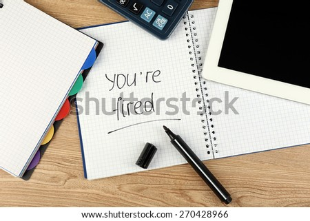 Message You're Fired on notebook on wooden table, closeup - stock photo