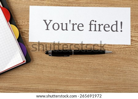 Message You're Fired on sheet of paper with pen on wooden table, top view - stock photo