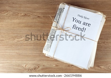 Message You're Fired on wooden background - stock photo