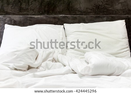 Messy and unmade bed in hotel room - stock photo
