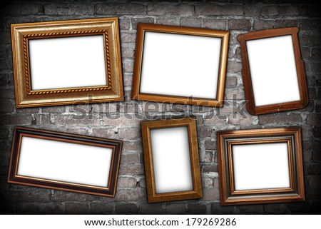 messy arrangement of wooden frames over grungy brick wall with place for text or message on white paper - stock photo