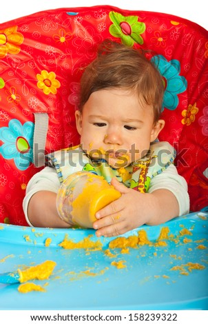 Messy baby boy eating puree by yourself and sitting in chair - stock photo