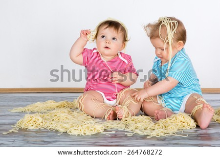 Messy baby toddlers having fun eating pasta - stock photo