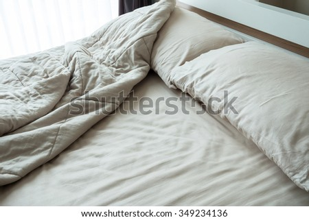 Messy bed with two pillows in the morning.