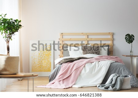Messy Bedding On Wooden Bed In Cozy Bright Bedroom