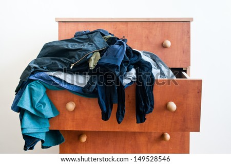 Messy brown chest of drawers with  dangling mixed man's and woman's clothes. - stock photo