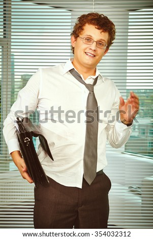 Messy businessman with briefcase looking at camera
