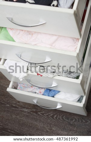 Messy clothes in wardrobe. Vertical photo