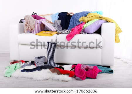 Messy colorful clothing on  sofa on light background - stock photo