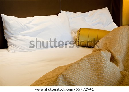 Messy luxurious bed with pillow and quilt cover