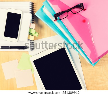 Messy office table with digital tablet, smartphone, reading glasses, notepad and filling folders. View from above with copy space - stock photo