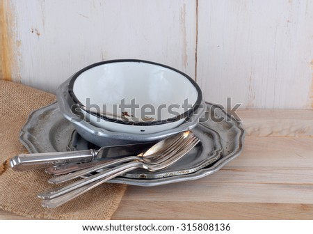 Messy stack of old pewter and enamelware dishes with tarnished silverplated utensils sitting on burlap on a wood table in front of white-washed wooden background with copy space. - stock photo