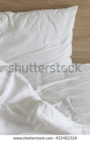 Messy white bed and pillow, in the morning, bedroom concept background.