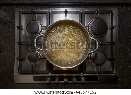 Metal aluminum pan on traditional iron stove cooker boiling water with chicken stock for cooking pasta - stock photo
