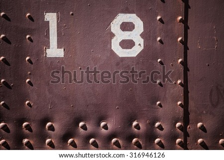 Metal background with number eighteen. Grunge background metal plate with screws - stock photo