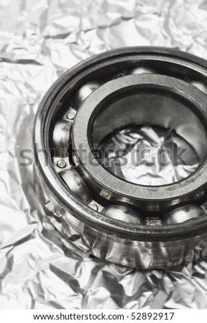 Metal ball bearing on creased aluminum sheet background - stock photo
