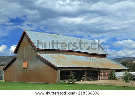 Metal barn with blue sky and clouds, Utah, USA. - stock photo