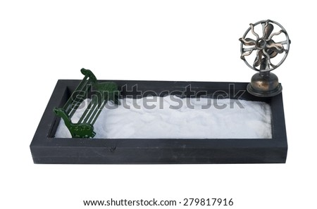 Metal Bench in an enclosed park filled with snow with a fan to show a cold wind - path included  - stock photo