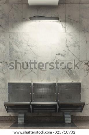 Metal bench on white marble background. Illuminated.  - stock photo