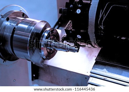 metal blank machining process on lathe with cutting tool - stock photo